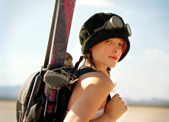 Portrait of a young woman carrying ski equipment on her back in a desert.