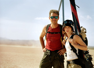Portrait of an adventurous couple carrying ski equipment while standing in the desert.