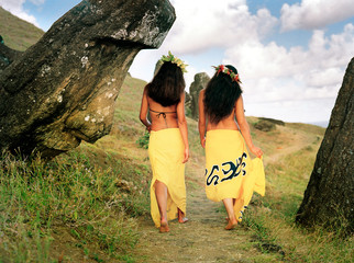 Two woman in traditional costume walking  through hills