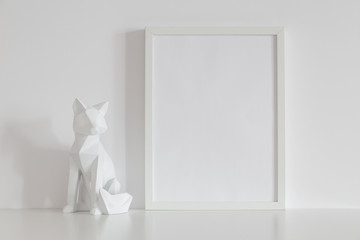 Blank frame and fox origami home decoration against white wall. on a shelf