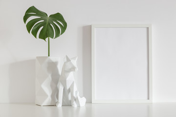 White frame mock up, origami vase decoration and monstera.