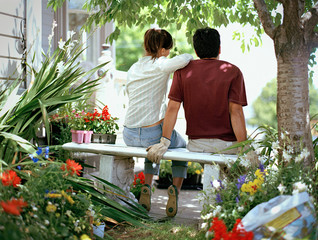 Rear view of young couple sitting next to each other on garden bench.