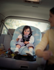 Young girl sitting with ice cream around her mouth in a carseat in the back of her mother's car.