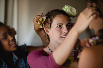 Teenage girls dressing each other's hair with roses.
