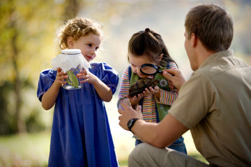 Girl with magnifying glass examining a turtle with her father.