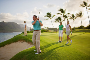Man and two women watch a male golfer take a shot over a beach sand trap.