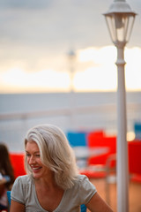 Happy mature woman sitting on cruise ship dock.