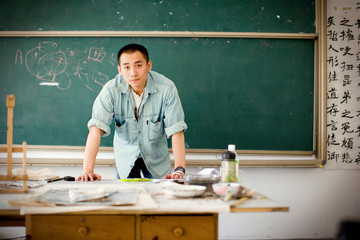 Portrait of a young adult man standing near a chalk board in a classroom.
