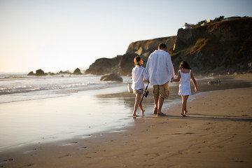 Father and two daughters walking along the beach