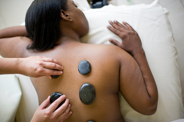 Young woman having warm stones placed on her bare back.