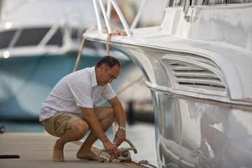 Mature man crouching while untying his boat from a wooden jetty.