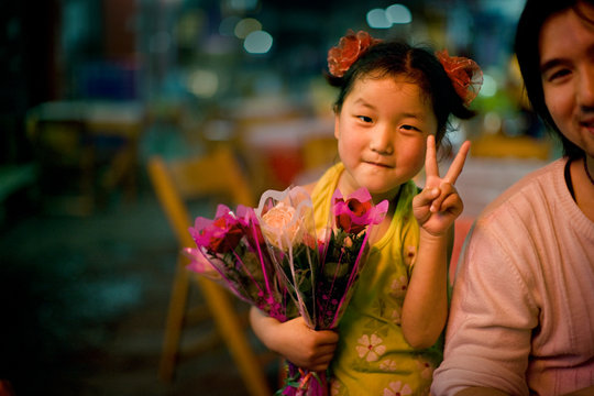 Girl making peace sign and smiling at the camera