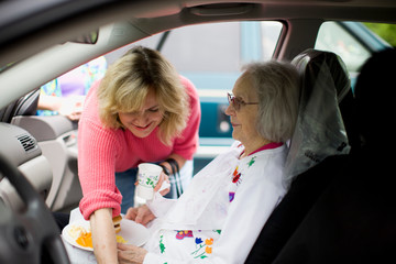 Mid-adult woman reaching over her elderly mother who is sitting inside a car.