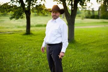 Man in cowboy hat holding cigar