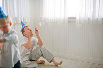 Boys Wearing Party Hats and Blowing Bubbles