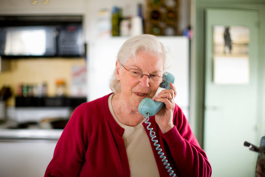 Senior woman speaking into a telephone inside her kitchen.