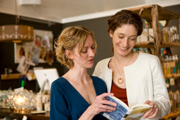 Two smiling woman looking at a book together inside a store.