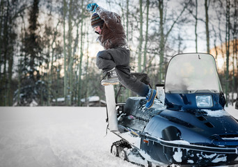 Happy young boy leaping off a snowmobile.