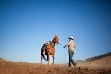 Rancher holding the reins of a horse.