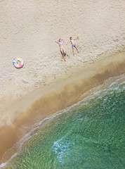 Adorable kids have fun on the beach. Aerial drone bird's eye view photo.
