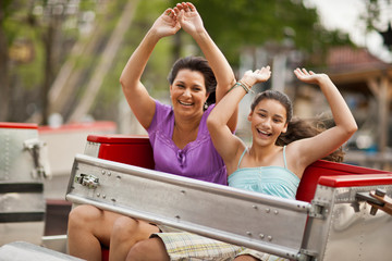Happy mother and daughter on a ride at an amusement park.