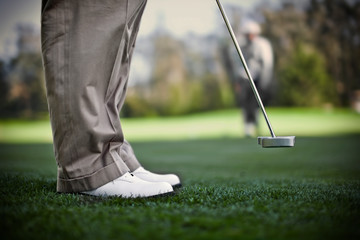 Pair of golf shoes standing on a golfing green.