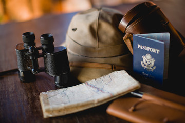 Passport a long with binoculars and a safari hat and notebook.