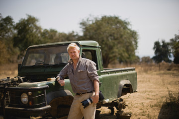 Mid-adult man standing beside a safari truck.