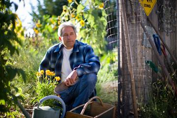 Mature man sitting in garden holding a trowel.