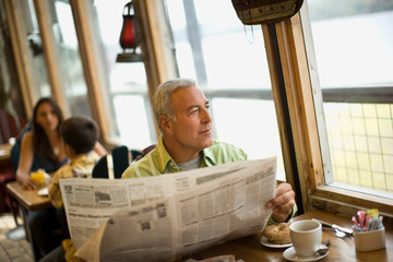 Mature man looking out a window while holding a newspaper inside a cafe.