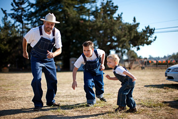 Father and two sons wearing matching denim overalls about to race
