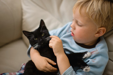 A young boy cuddles his cat.