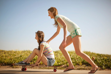 Young woman pushing her friend who is sitting on a skateboard