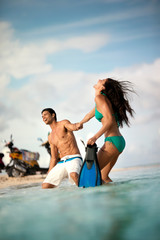 Happy mid adult couple wading in shallow water at the beach.