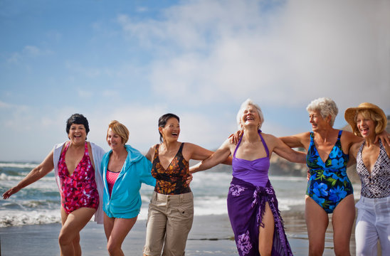 Happy mature friends enjoying a day at the beach.