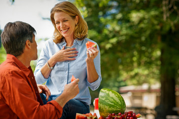 Happy middle aged couple enjoying watermelon during a picnic in the park.