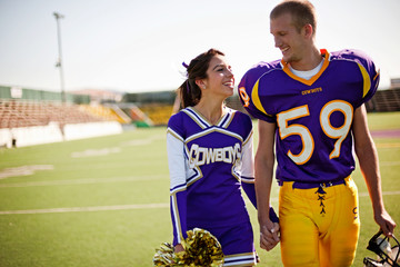 Football player and cheerleader holding hands on football field