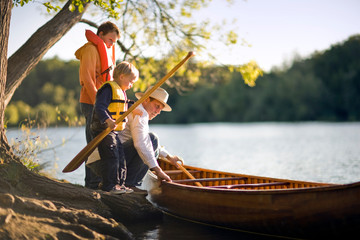 A father and his young sons prepare to go canoeing.