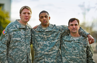 Portrait of three US Army soldiers with their arms around each other.