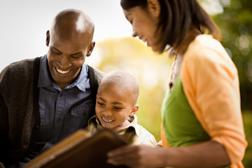 Young heterosexual couple read a book to their young son.