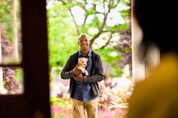 Smiling young man holding a puppy as seen through a doorway.