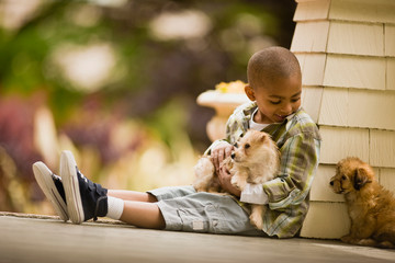 Smiling young boy sits on a porch holding one puppy and looking down at another puppy sitting next to him.