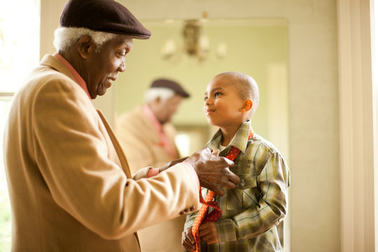 Senior man helping his grand son tie his tie.