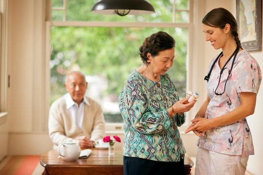 Smiling nurse giving a senior woman pill bottles.