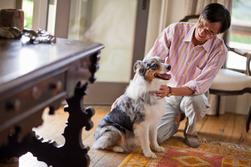Smiling middle aged man petting his dog.