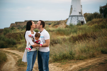 Happy young family in white t-shirts and blue jeans with a small daughter near to the white lighthouse, outdoors background