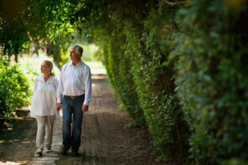 Mature couple walking down country road holding hands.