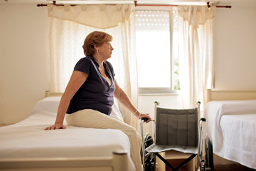 Mature female patient sitting on hospital bed.