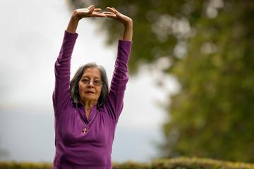 Senior woman practicing yoga in her back yard.