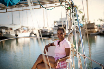 Portrait of mature woman happily relaxed as she is sitting on boat deck in harbour.